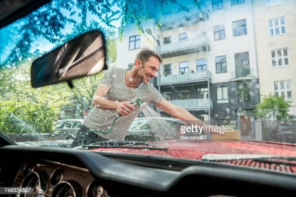 smiling mature man washing his car - waschen stock-fotos und bilder