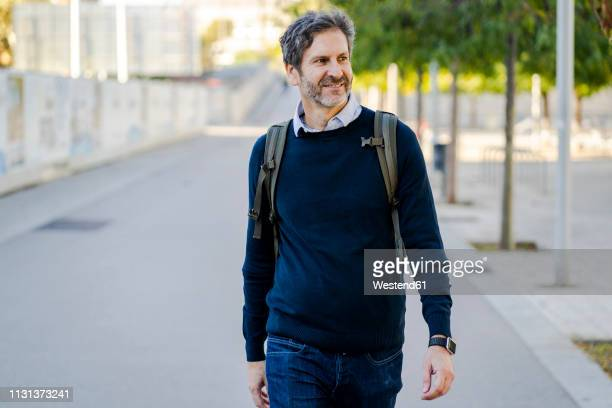 smiling mature man with a backpack in the city on the go - un seul homme photos et images de collection