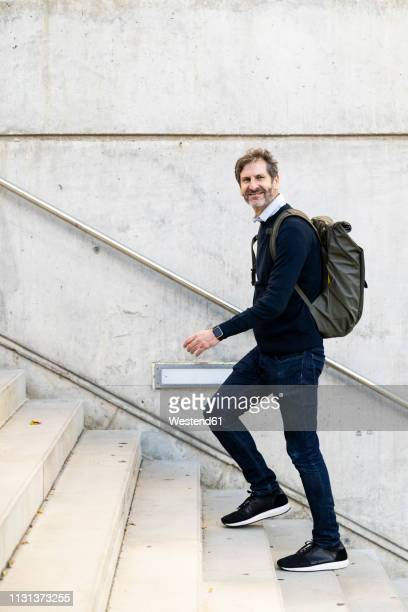 smiling mature man with a backpack walking up stairs in the city - moving up stock pictures, royalty-free photos & images