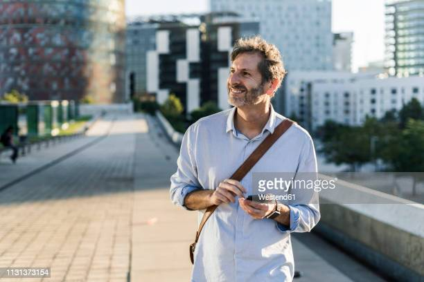 smiling mature man with cell phone in the city - shoulder bag stock pictures, royalty-free photos & images
