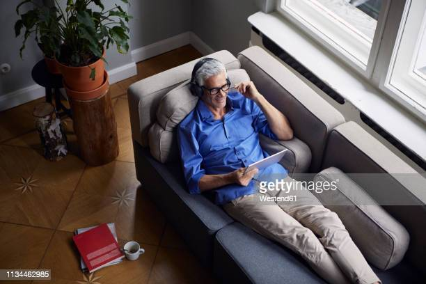 smiling mature man with tablet and headphones relaxing on couch at home - blue film video stock pictures, royalty-free photos & images
