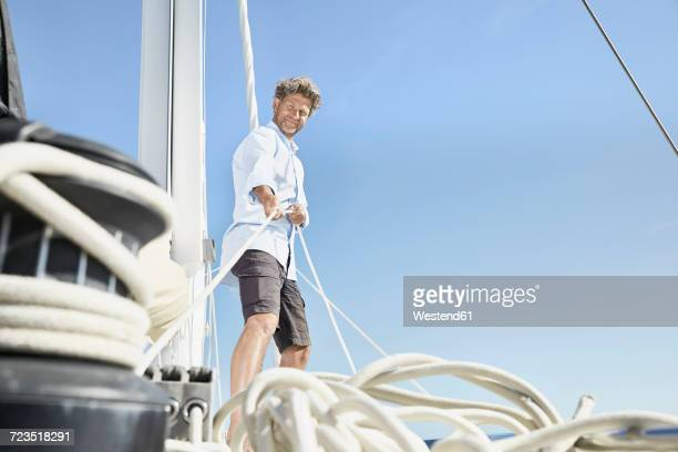 Smiling mature man working with ropes on sailing boat