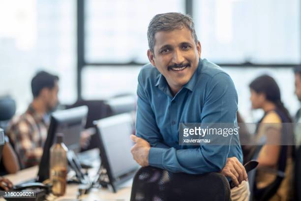smiling mature manager sitting at creative office - indian subcontinent ethnicity stock pictures, royalty-free photos & images