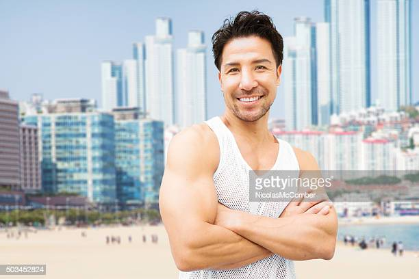 smiling mature muscular japanese man beach portrait arms crossed - muscle men at beach stock photos and pictures