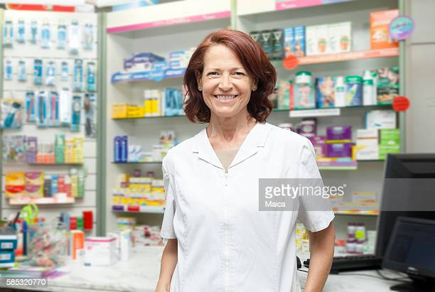 Smiling mature professional pharmacist at her store