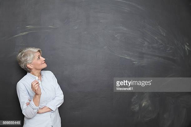 Smiling mature teacher looking at blackboard