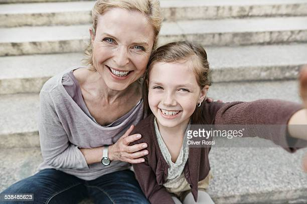 smiling mature woman and girl looking at camera - シュラッグ ストックフォトと画像