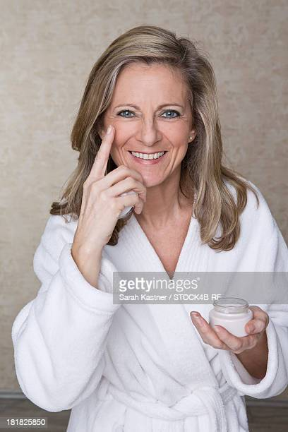 Smiling mature woman applying facial cream