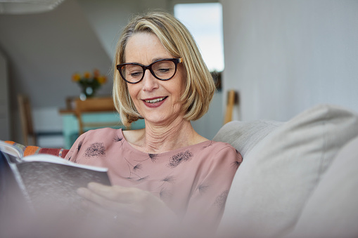 Smiling mature woman at home on the sofa reading a book - gettyimageskorea