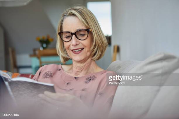 smiling mature woman at home on the sofa reading a book - reading stock pictures, royalty-free photos & images