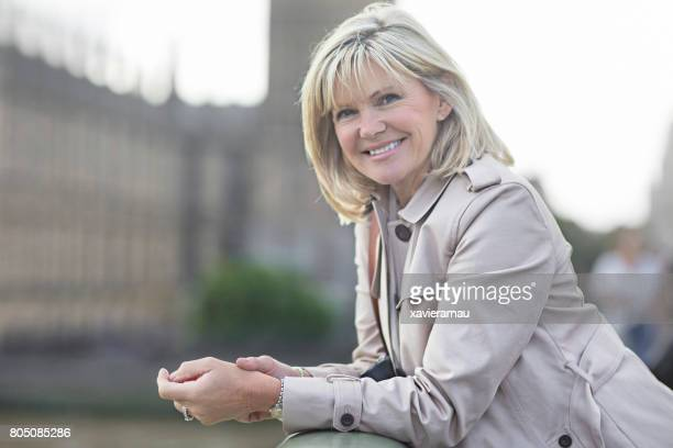 Lachende rijpe vrouw in Westminster Bridge