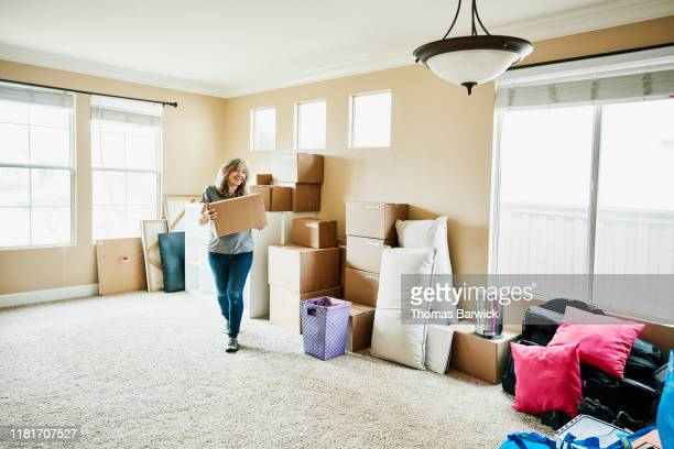smiling mature woman carrying box while moving into new home - carrying stock pictures, royalty-free photos & images