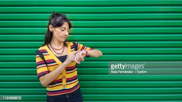 smiling mature woman checking time against green - corrugated iron stock photos and pictures