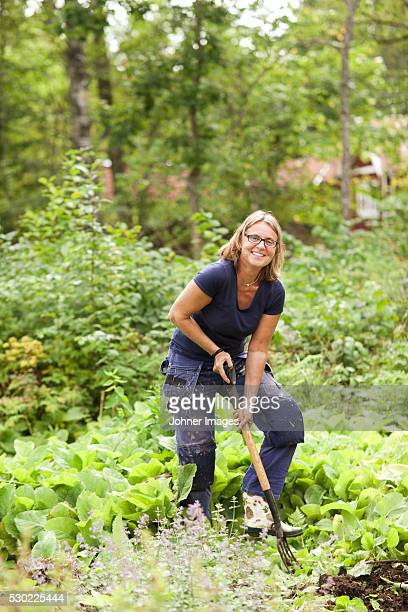 smiling mature woman digging in garden - one mature woman only stock pictures, royalty-free photos & images