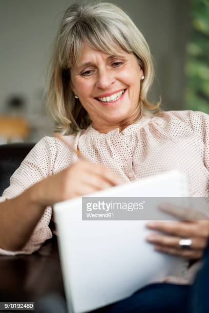 Smiling mature woman drawing on sketchbook