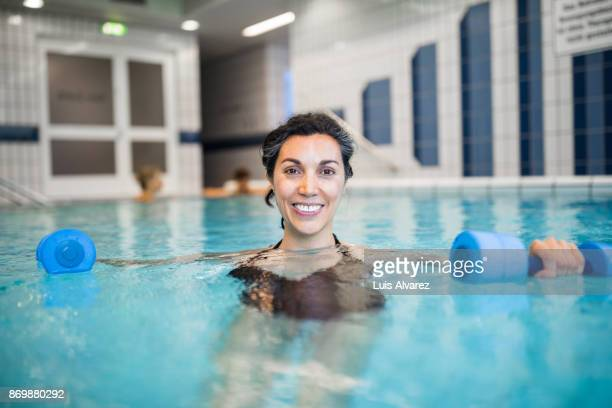smiling mature woman exercising with dumbbells in swimming pool - hydrotherapy stock photos and pictures