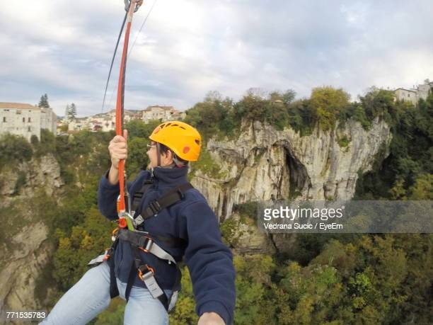 Smiling Mature Woman Hanging On Zip Line Over Trees Against Sky