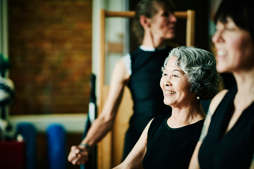 Smiling mature woman hanging out with friends in pilates studio while resting between exercises - gettyimageskorea