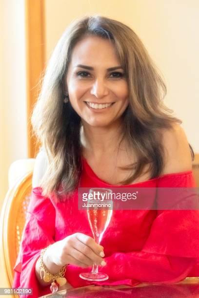 シャンパンのグラスを持って笑顔の熟女 - イラン人 ストックフォトと画像