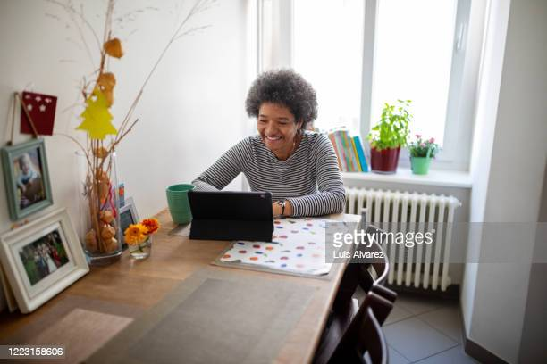 smiling mature woman having video call during home quarantine - disruptaging stock pictures, royalty-free photos & images