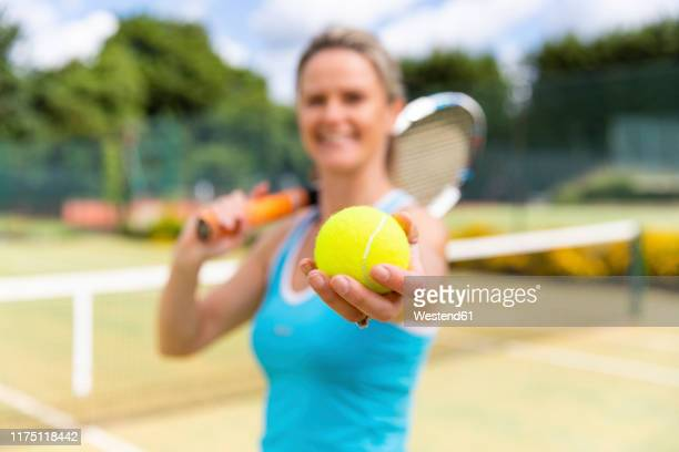 smiling mature woman holding a tennis ball at tennis club - tennis player stock pictures, royalty-free photos & images