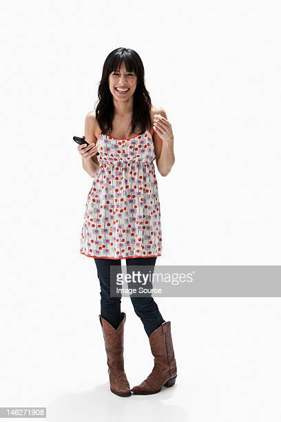 Smiling mature woman holding cellphone, studio shot
