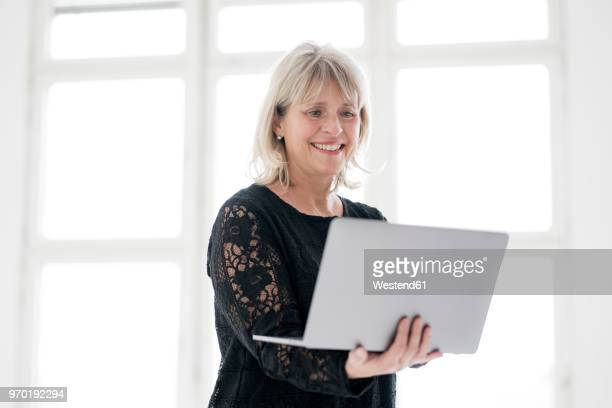 Smiling mature woman holding laptop