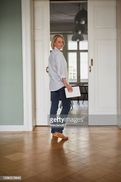 smiling mature woman holding tablet at home - tourner photos et images de collection