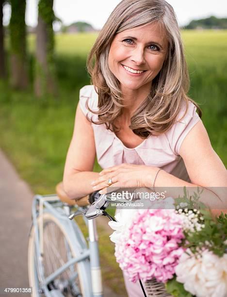 Lächelnd Reife Frau in einem park mit ihren Fahrrädern