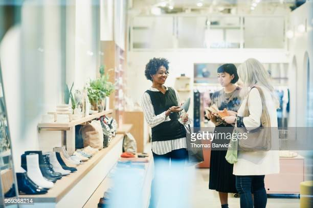 smiling mature woman in discussion with store owner while shopping for shoes with friend - women wearing see through clothing stock pictures, royalty-free photos & images