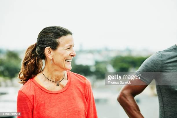 smiling mature woman in discussion with workout partner - parte mediana imagens e fotografias de stock