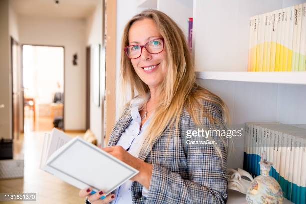 smiling mature woman in formalwear holding a book - authors stock pictures, royalty-free photos & images