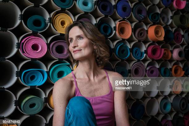 Smiling mature woman in front of assortment of yoga mats
