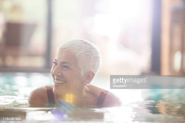 スイミングプールで笑顔の成熟した女性 - 室内プール ストックフォトと画像
