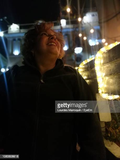 Smiling Mature Woman Looking At Illuminated Lights At Night