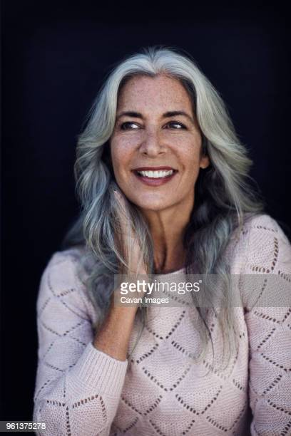 smiling mature woman looking away against blue background - beautiful woman chest stock pictures, royalty-free photos & images