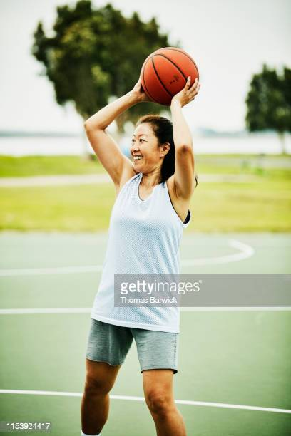 smiling mature woman looking to make pass during basketball game on outdoor court - passing sport stockfoto's en -beelden