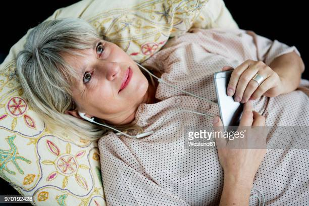 Smiling mature woman lying down with cell phone and earphones