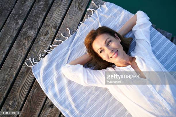 smiling mature woman lying on a towel on a jetty at a lake - tagträumen stock-fotos und bilder
