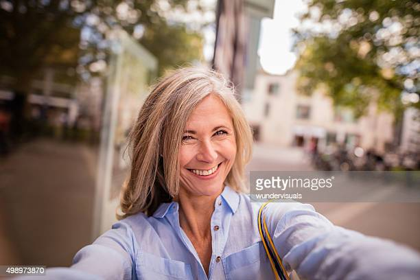 Smiling mature woman on a city street taking fun selfie