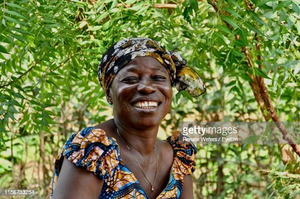smiling mature woman outdoors against tree - ghana africa fotografías e imágenes de stock