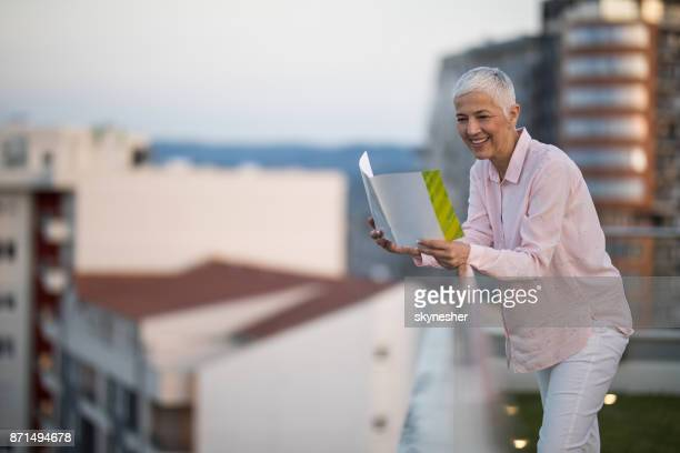 smiling mature woman reading a magazine on a penthouse balcony. - penthouse magazine photos stock pictures, royalty-free photos & images