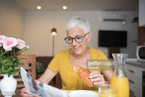 Reife Frau lesen Zeitungen lächelnd