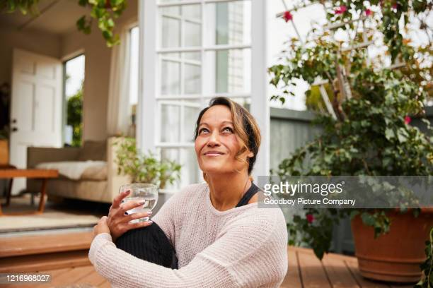 smiling mature woman relaxing on her patio at home - drinking water stock pictures, royalty-free photos & images