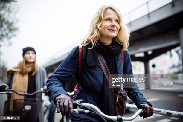 smiling mature woman riding bicycle with friend - 45 49 years stock pictures, royalty-free photos & images