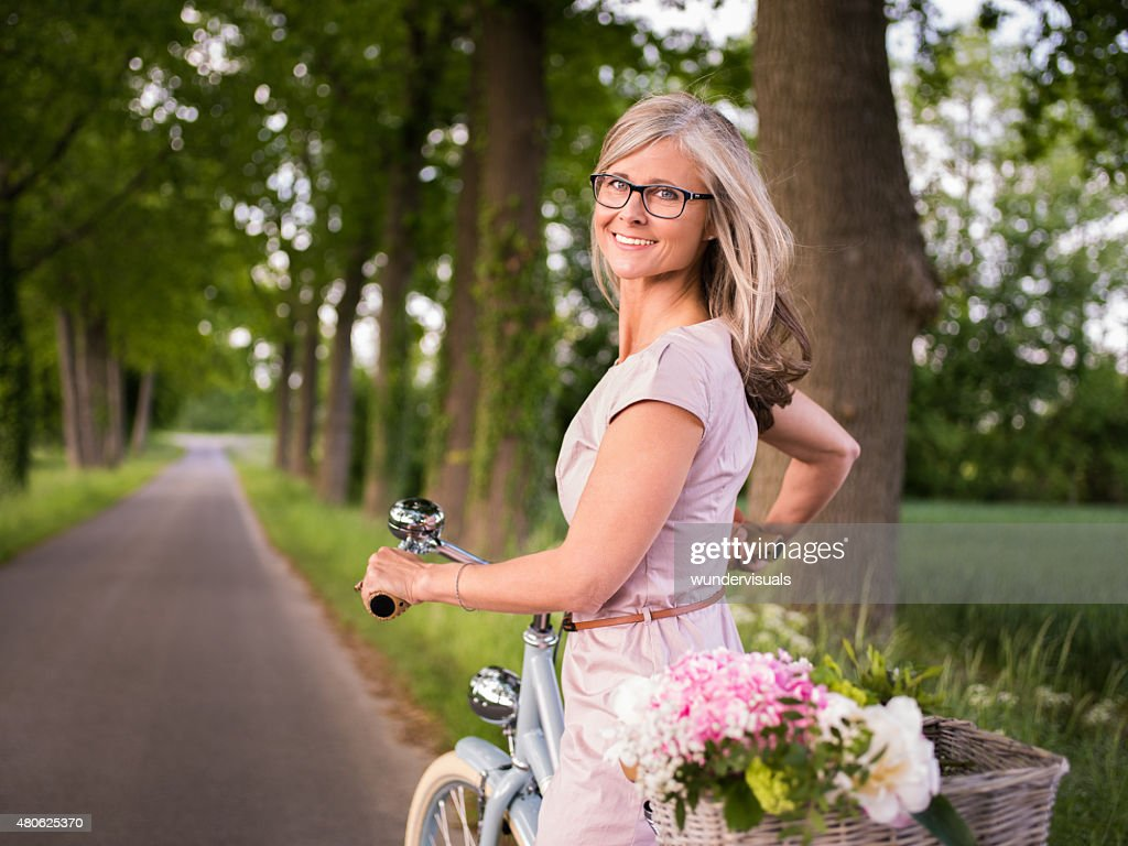 smiling mature woman riding her bicycle in a park stock photo