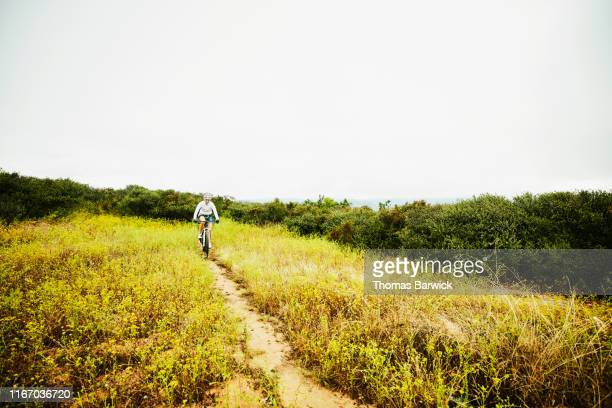 smiling mature woman riding through meadow during early morning mountain bike ride - mid distance stock pictures, royalty-free photos & images