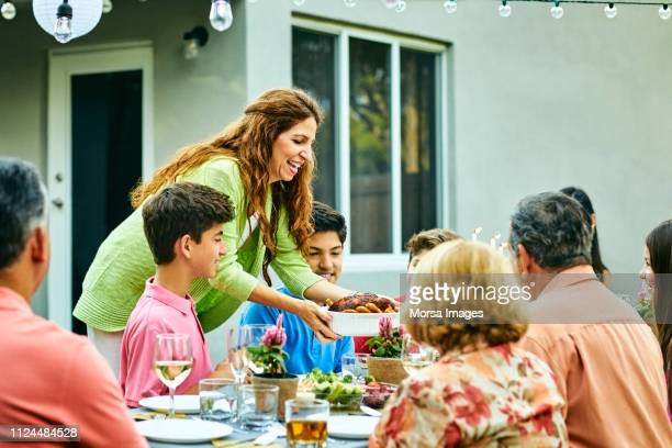 smiling mature woman serving food at dining table - serving food and drinks stock pictures, royalty-free photos & images