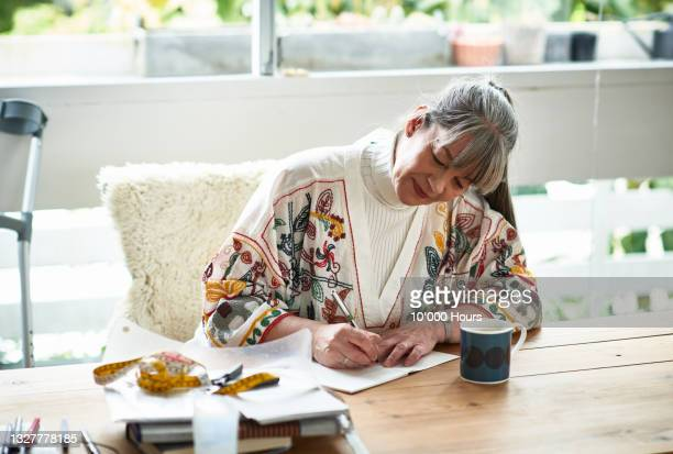 smiling mature woman sitting writing in notebook - writer stock pictures, royalty-free photos & images