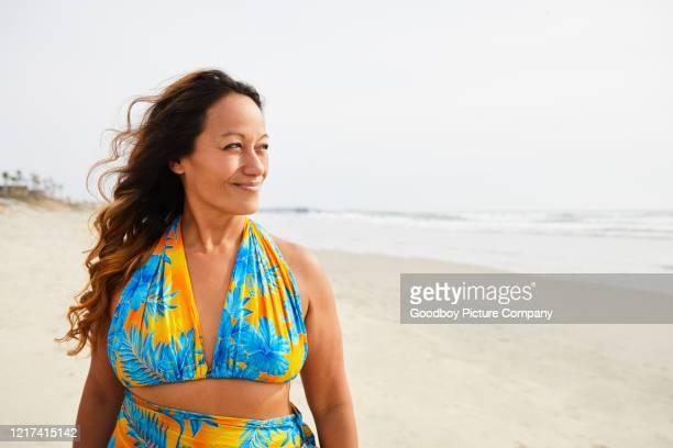 femme mûr de sourire restant seul sur une plage sablonneuse - une seule femme d'âge mûr photos et images de collection